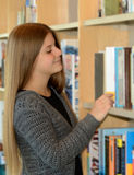 Young pretty girl browsing books. She enjoys her activity Stock Images