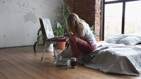 Young pretty girl with brush and palette sitting near easel drawing picture. Art, creativity, hobby, drawing process. Young pretty blonde girl with brush and stock video