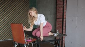 Young pretty girl with brush and palette sitting near easel drawing picture. Art, creativity, hobby, drawing process. Young pretty blonde girl with brush and stock footage