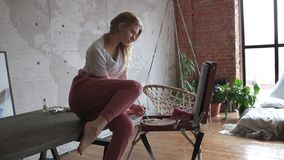 Young pretty girl with brush and palette sitting near easel drawing picture. Art, creativity, hobby, drawing process. Young pretty blonde girl with brush and stock video footage