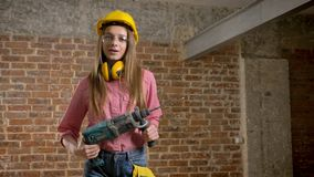 Young pretty girl builder is holding drill in her hands, turning on, smiling, building conception.  stock footage