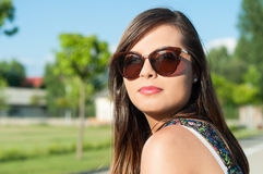 Young pretty girl close-up posing wearing sunglasses. Outside in park in sunlight with copy text space Royalty Free Stock Photos