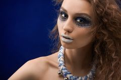 The picture of a beatiful girl with the original make-up. A young pretty girl with colorful ornament painted on her face. She has healthy skin tone and brown Royalty Free Stock Photography