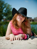 Young pretty girl in cowboy hat. Lies on sand Royalty Free Stock Image