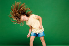 Young pretty girl dancing over green background. Royalty Free Stock Image