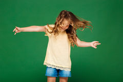 Young pretty girl dancing over green background. Royalty Free Stock Photo