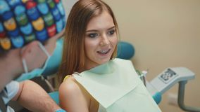 Young pretty girl is in dental cabinet on treatment and consultating. 4K stock footage