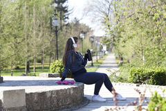Young pretty girl doing exercise and running in the park. Beautiful young woman is resting during exercise and drinking water in the park. Selective focus and Royalty Free Stock Images