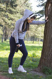 Young pretty girl doing exercise and running in the park. Beautiful young woman is resting during exercise in the park. Selective focus and small depth of field Stock Photos