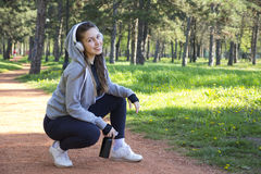 Young pretty girl doing exercise and running in the park. Beautiful young woman is resting during exercise in the park. Selective focus and small depth of field Stock Image
