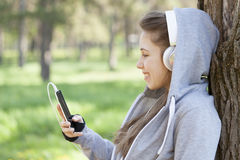Young pretty girl doing exercise and running in the park. Beautiful young woman using a mobile phone and resting during exercise in the park. Selective focus and Royalty Free Stock Images