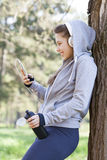 Young pretty girl doing exercise and running in the park. Beautiful young woman using a mobile phone and resting during exercise in the park. Selective focus and Royalty Free Stock Photography