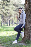 Young pretty girl doing exercise and running in the park. Beautiful young woman using a mobile phone and resting during exercise in the park. Selective focus and Stock Photography