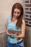 Young pretty girl doing on-line shopping using tablet. Urban bac Stock Photo