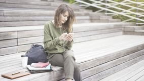 A young girl is texting on the phone outdoors sitting on the stairs. A young pretty girl dressed in a green sweat shirt is listening to music outdoors sitting on stock photo