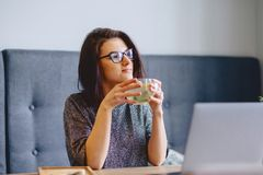 young pretty girl drinking hot tea with lemon for a laptop stock photos