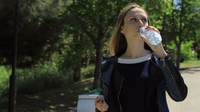 Young pretty girl drinking mineral water stock footage