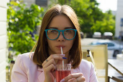 Young pretty girl drinks a cold beverage, outdoor Royalty Free Stock Photography