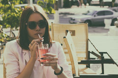 Young pretty girl drinks a cold beverage, outdoor Royalty Free Stock Images