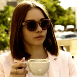 Young pretty girl drinks a cup of hot beverage, outdoor Stock Photography