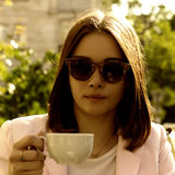 Young pretty girl drinks a cup of hot beverage, outdoor Royalty Free Stock Images