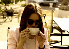Young pretty girl drinks a cup of hot beverage, outdoor Stock Photos