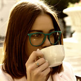Young pretty girl drinks a cup of hot beverage, outdoor Royalty Free Stock Image
