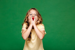 Young pretty girl eating raspberry over green background. Royalty Free Stock Photography