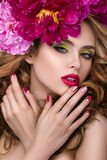Young pretty girl with flower wreath. Close-up beauty portrait of young pretty girl with flower wreath in her hair wearing bright pink lipstick and touching her Stock Photo