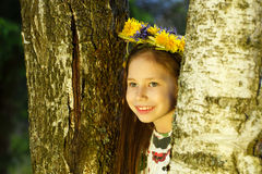 Young pretty girl in flowers wreath is looking out of birch tree. Stock Image