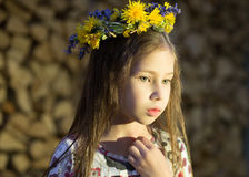 Young pretty girl in flowers wreath is staying near the woodpile  in the village. Royalty Free Stock Photo