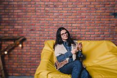 young pretty girl in glasses with a telephone on a sofa against stock photography