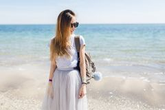 Young pretty girl in gray T-shirt and lush skirt is standing near sea. She has long hair and bag on her back. She is.  stock photos