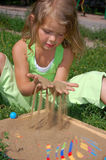 Young pretty girl hair playing with sand Royalty Free Stock Photos