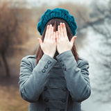 Young pretty girl with hands over eyes. Outdoors stock photos