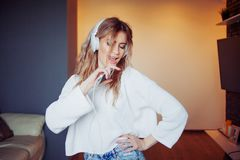 Young pretty girl in headphones with the phone. Listening to music, dancing and singing, indoors Stock Image