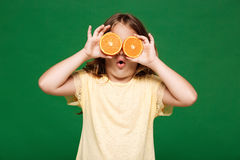 Young pretty girl hiding eyes with oranges over green background. Young pretty girl hiding eyes with oranges, mouth opened over green background. Copy space Stock Photos