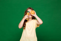 Young pretty girl hiding eyes with oranges over green background. Royalty Free Stock Photography