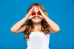 Young pretty girl hiding eyes with strawberry over blue background. Young pretty girl hiding eyes with strawberry, smiling over blue background. Copy space Royalty Free Stock Images