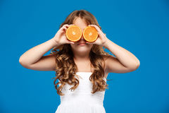 Young pretty girl hiding eyes wit oranges over blue background. Young pretty girl hiding eyes wit oranges, smiling over blue background. Copy space Stock Photos