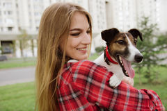 Young pretty girl hold her dog. Rear view. Close up. Stock Photo