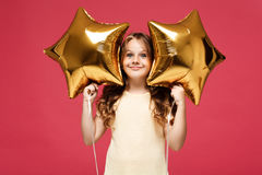Young pretty girl holding baloons and smiling over pink background. Royalty Free Stock Image