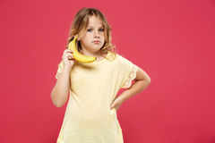 Young pretty girl holding banana like phone over pink background. Royalty Free Stock Images