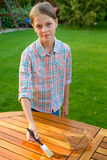 Young pretty girl holding a brush applying varnish paint on a wooden garden table Royalty Free Stock Photos