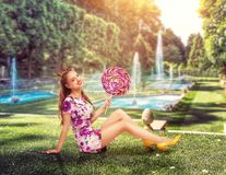 Young pretty girl holding a huge colorful lollypop. Amasing young woman sits on green grass holding big candy in her hands. Stylish girl in summer dress, park Stock Image