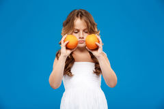 Young pretty girl holding oranges over blue background. Stock Photos