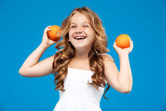 Young pretty girl holding oranges, smiling over blue background. Royalty Free Stock Photos
