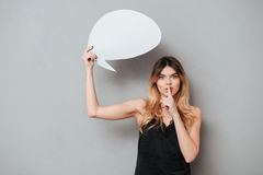 Young pretty girl holding speech bubble and showing silence gesture Royalty Free Stock Photography