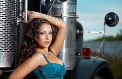 Young pretty girl in jeans stand near steel truck Stock Photo