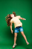 Young pretty girl jumping over green background. Stock Photo